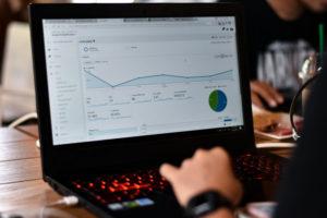 webmaster analyzing SEO and google analytics on laptop